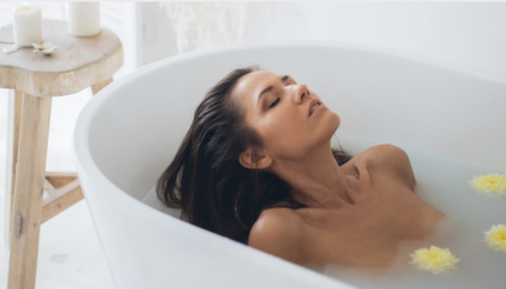 Woman relaxing in a bathtub with a bath bomb and floating flowers