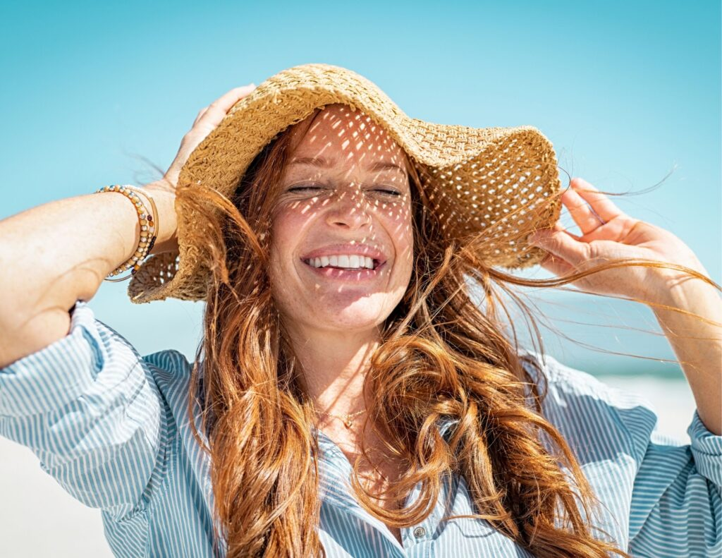 Woman at the beach wearing a sunhat smiling and closing her eyes in the sun